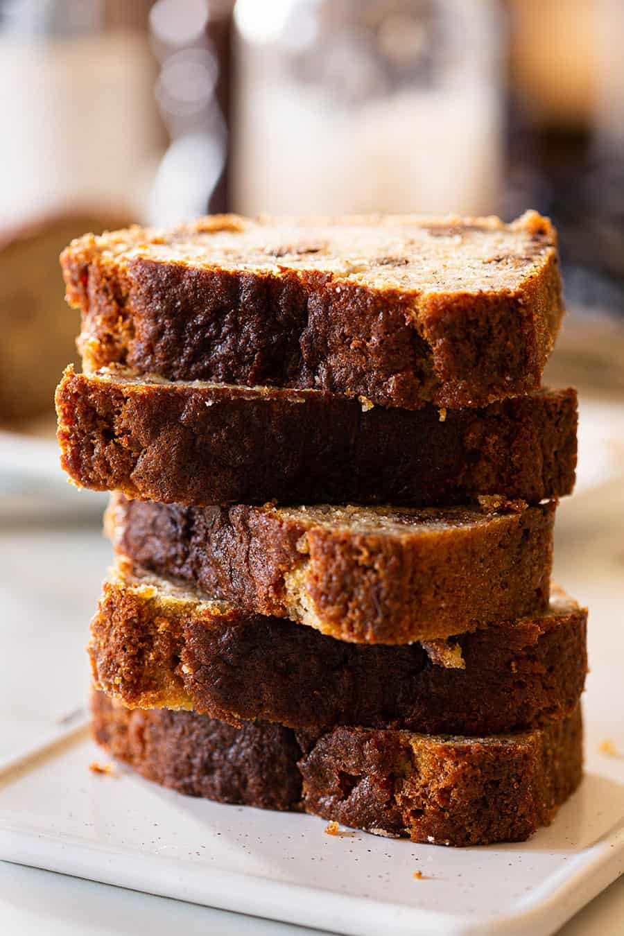 Chocolate chip banana bread cut into slices and piled on a white serving plate.