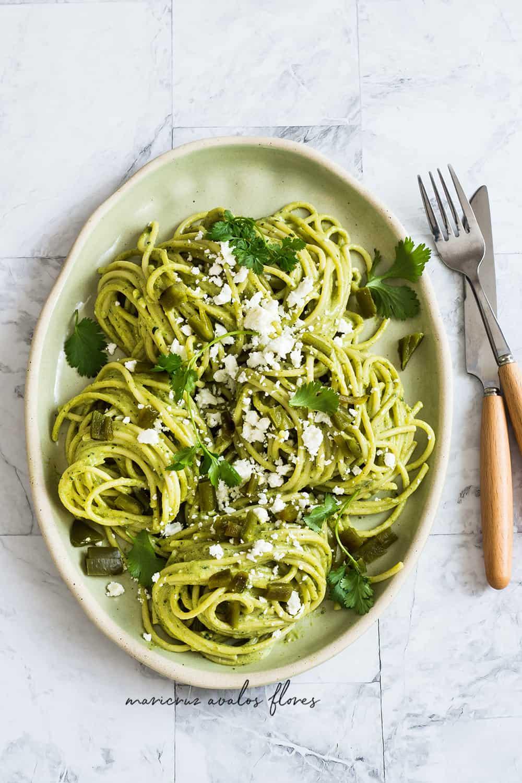 Espagueti Verde servido en una fuente con queso fresco espolvoreado encima.