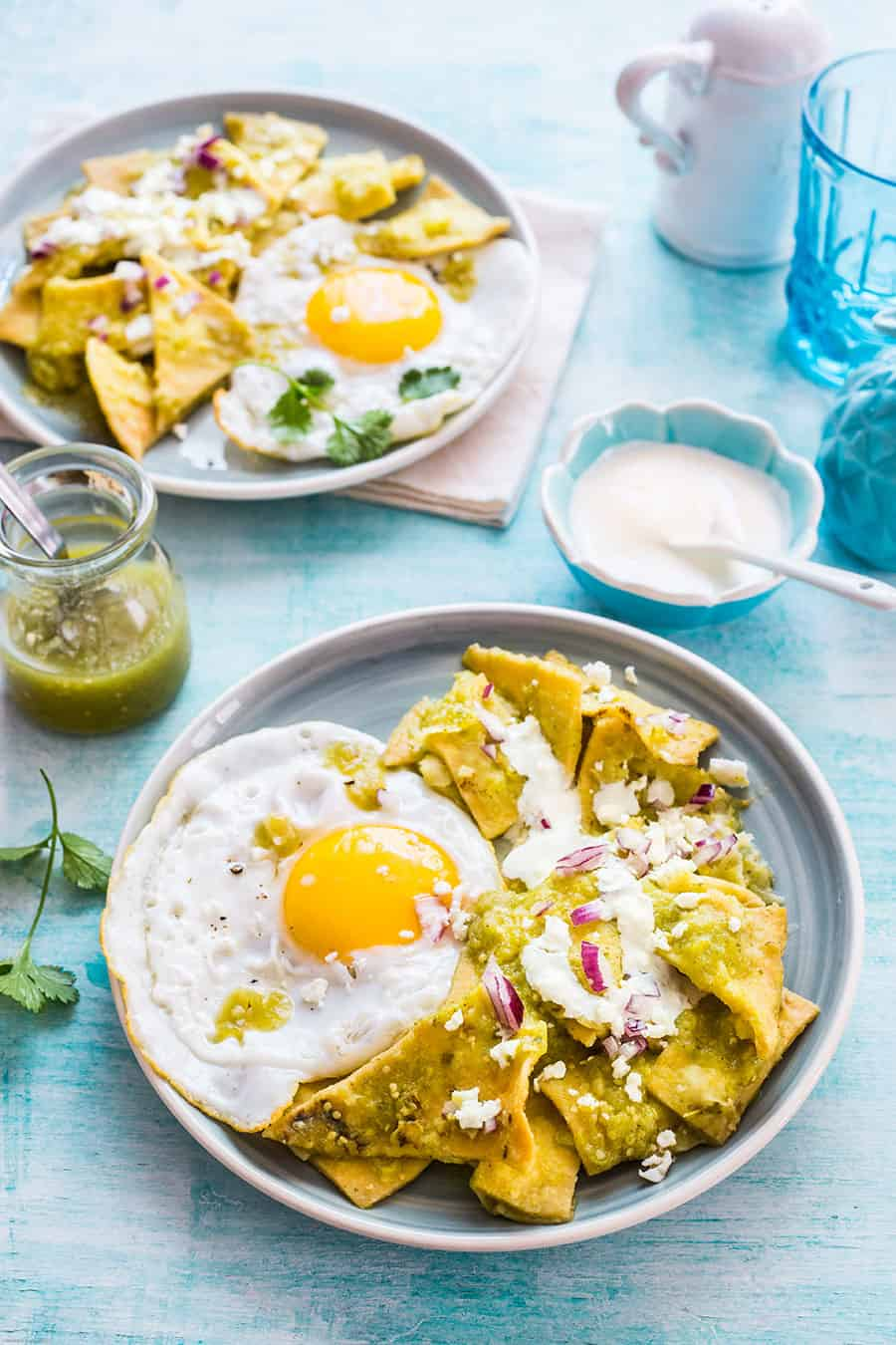 Chilaquiles verdes served with a fried egg on top.