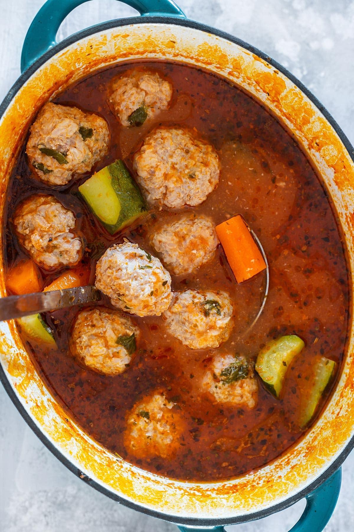 Mexican meatball soup (caldo de albóndigas) on a cast iron pot.