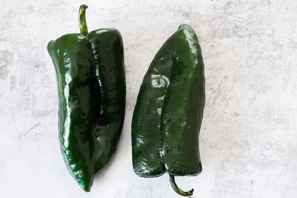 Raw poblano peppers on a surface.