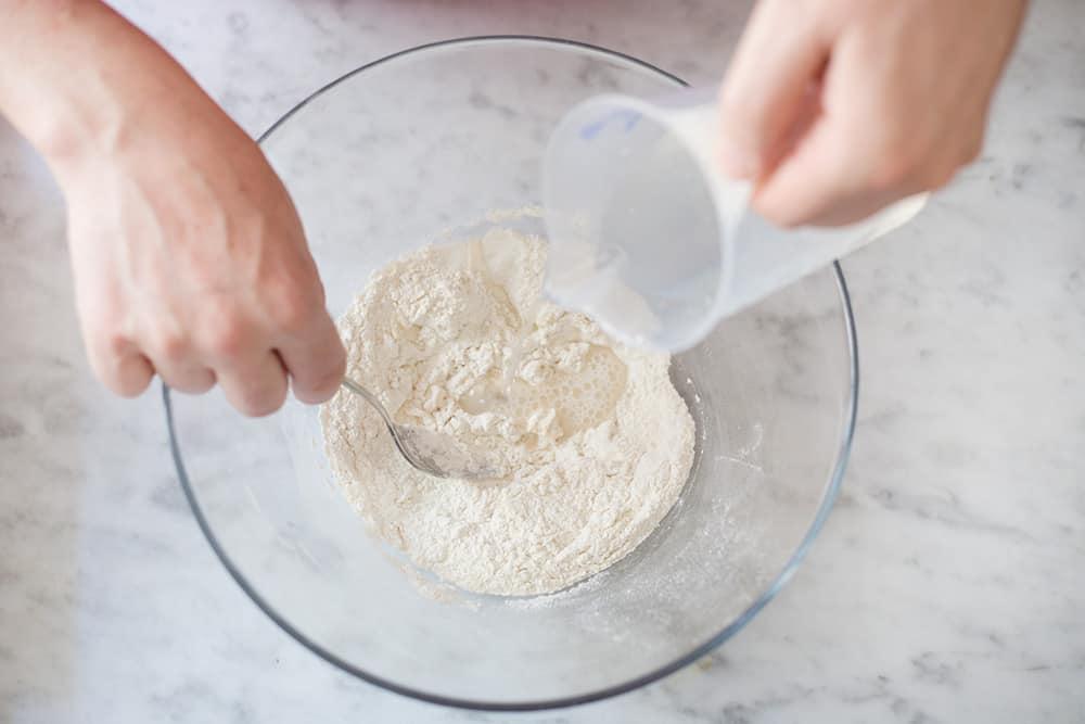 poniendo agua en el cuenco con la harina para hacer una hogaza de pan fácil