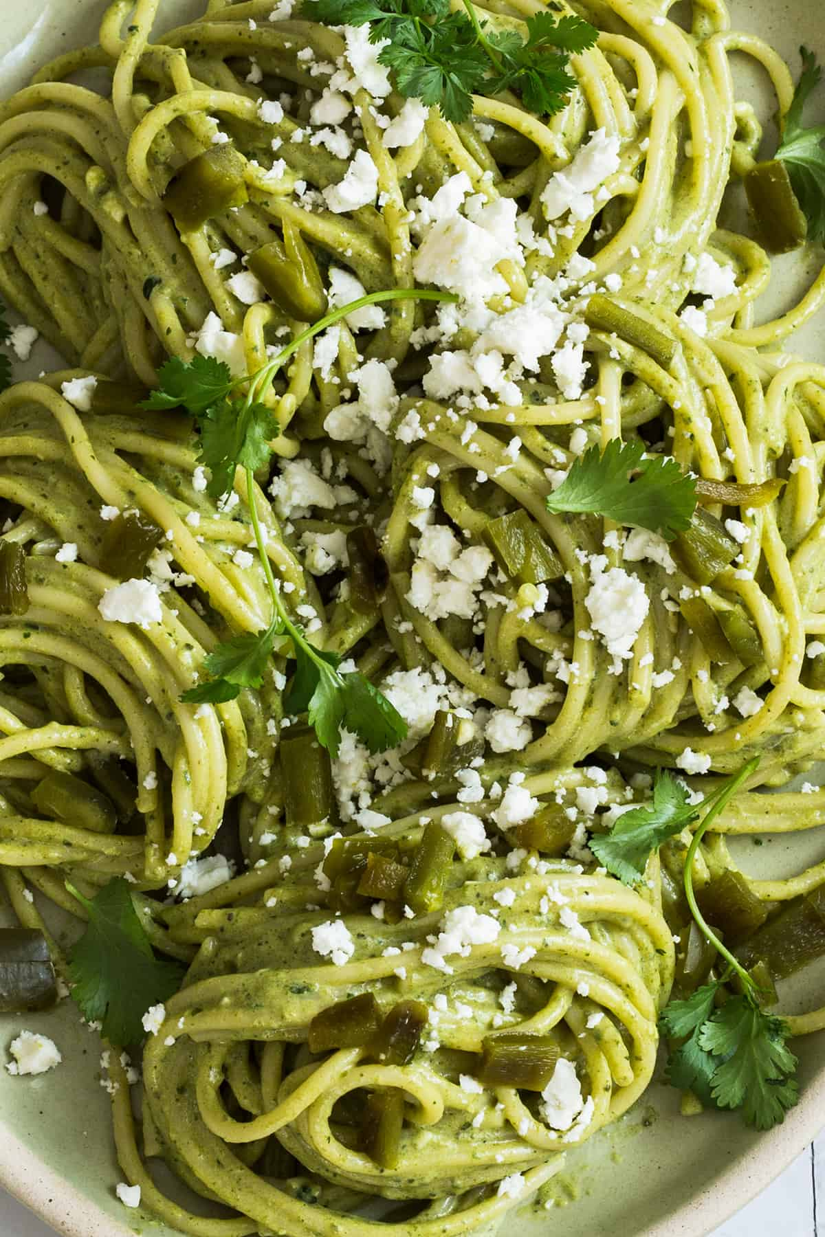 A close up to a creamy mexican green spaghetti with queso fresco.