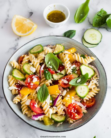 A bowl of mediterranean pasta salad, full of brilliant colours
