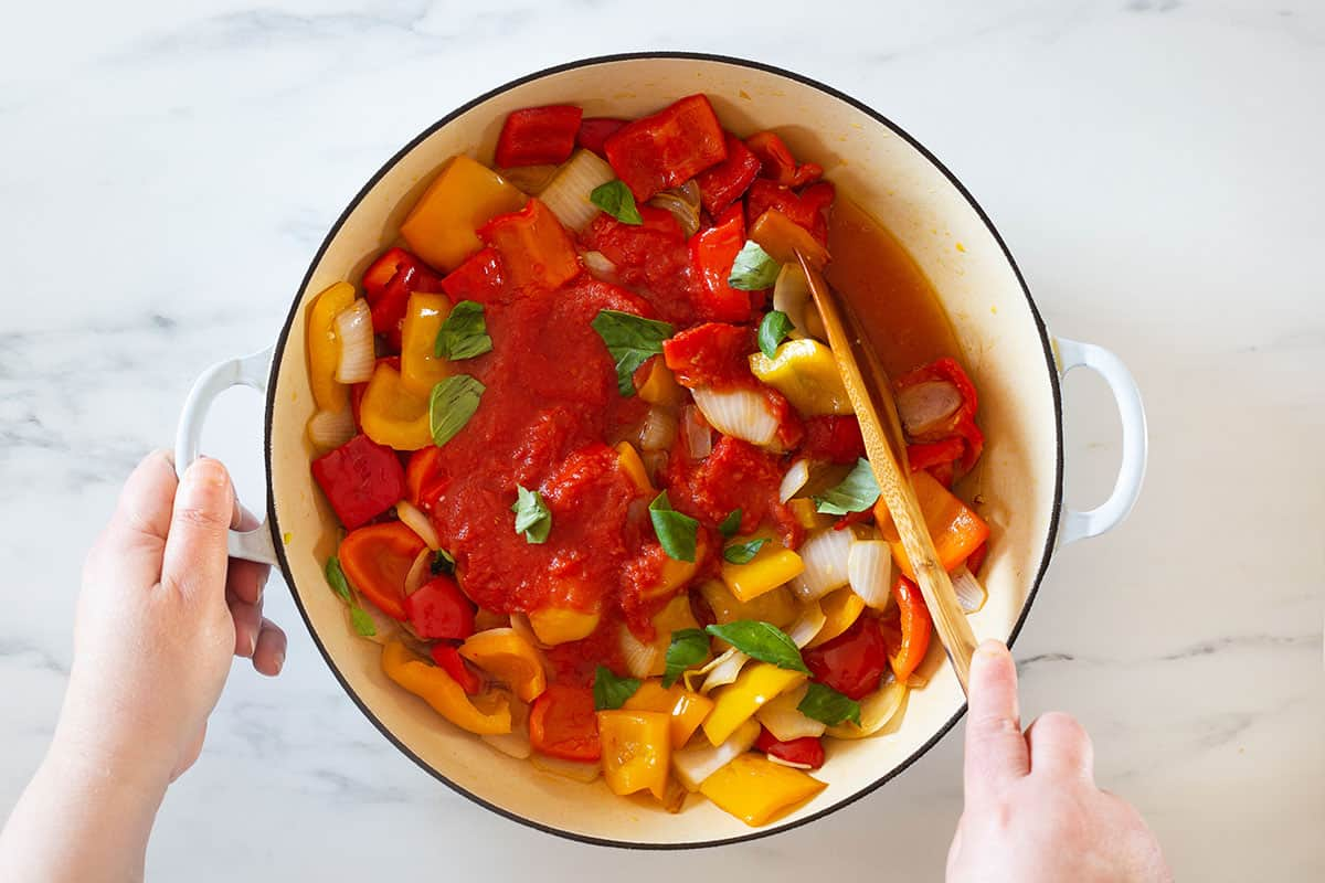 Adding tomato sauce and basil to the pan with peppers and onions.