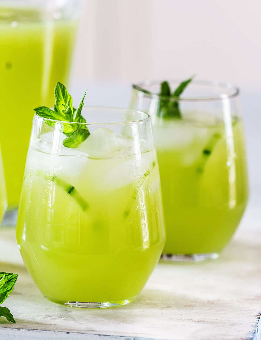 Agua de pepino (cucumber water) served on glasses with ice, mint leaves and cucumber slices.