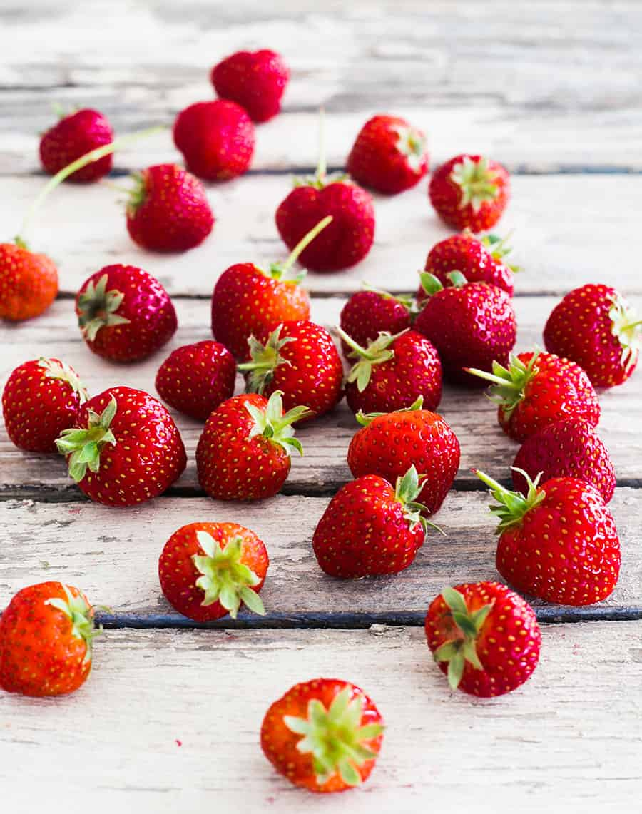 Fresas frescas, enteras, sobre una superficie de madera blanca.