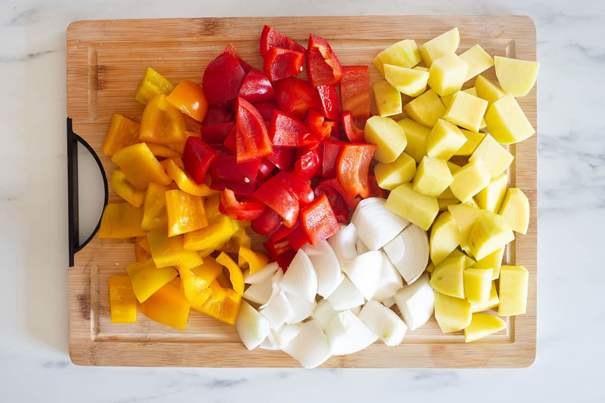 Yellow and red bell peppers alongside with onions and potatoes on a cutting board.