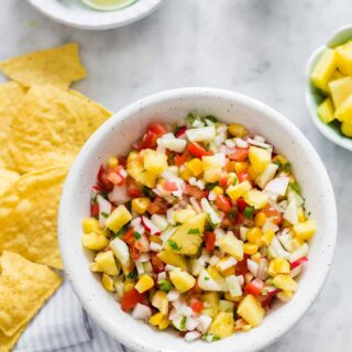 a bowl of fresh pineapple pico de gallo displayed on white surface