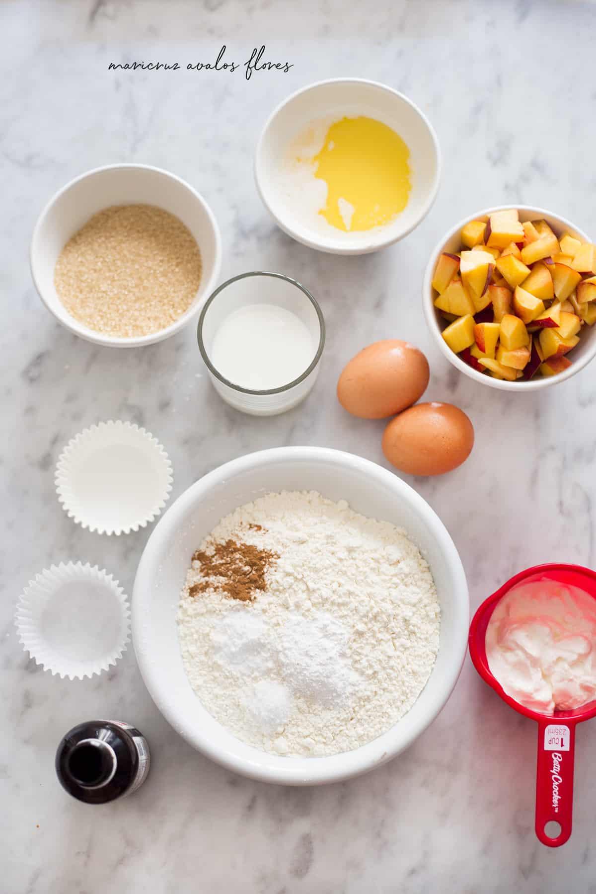 ingredientes para muffins de duraznos (mantequilla, azúcar, harina, fruta, huevos, vainilla).