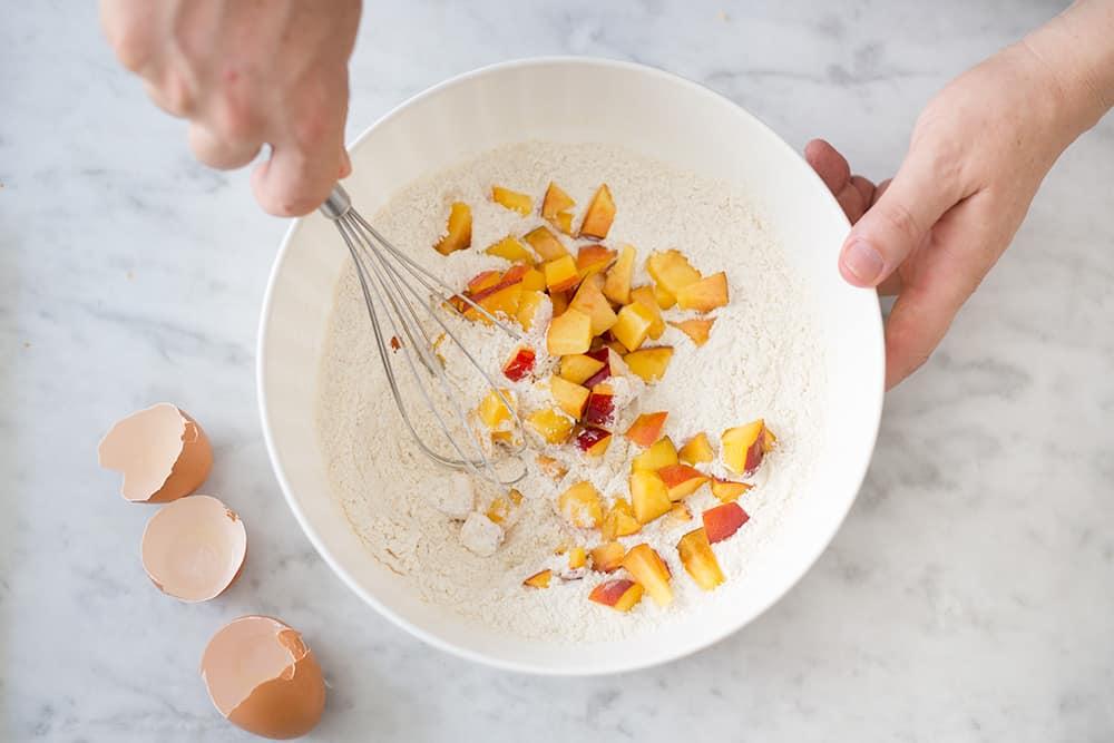 preparación de muffins de durazno (mezclando la harina con la fruta)