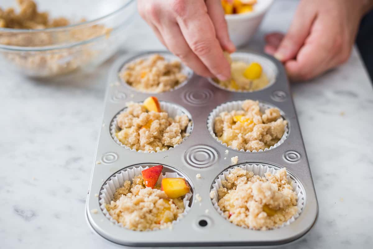 adding crumble to Peach streusel muffins