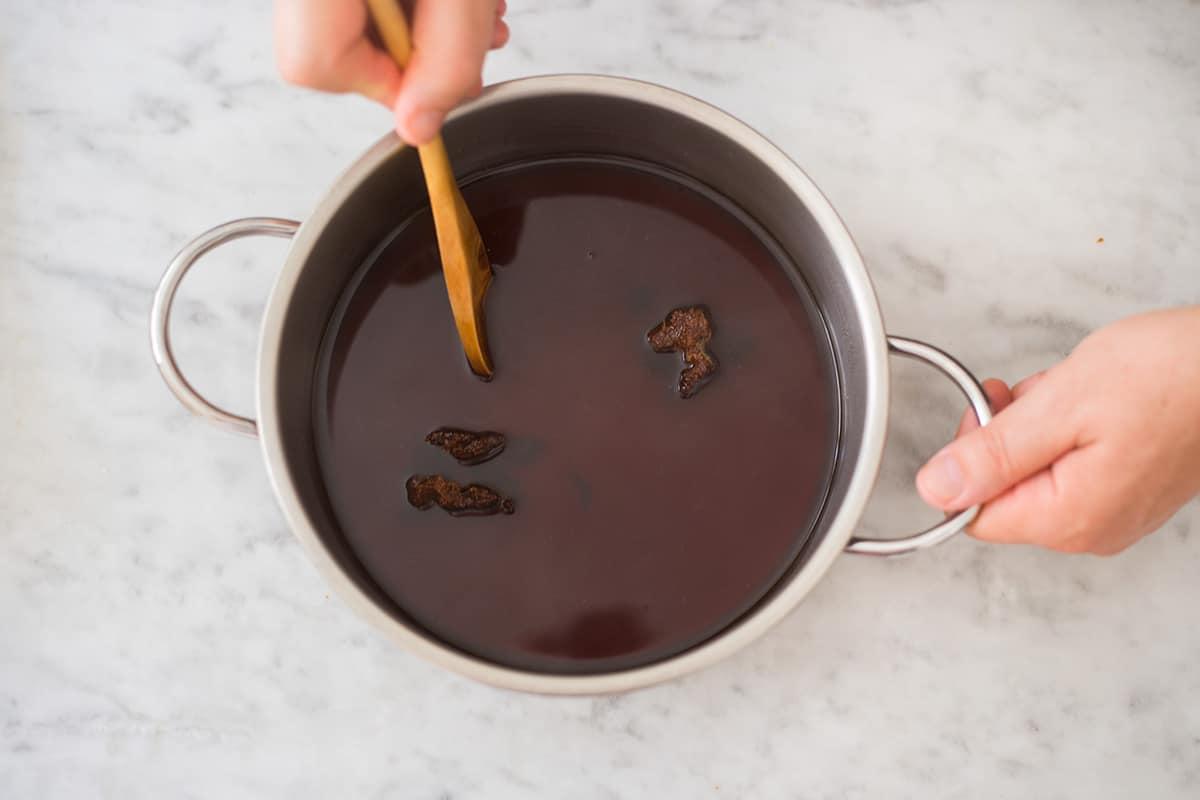 Mezclando el piloncillo con agua en una olla.