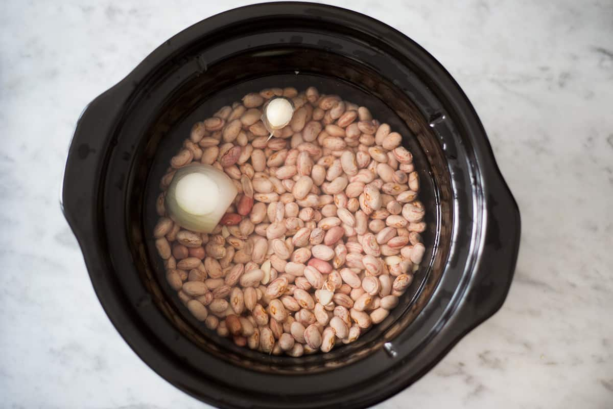 Beans with onions and garlic on a crockpot.