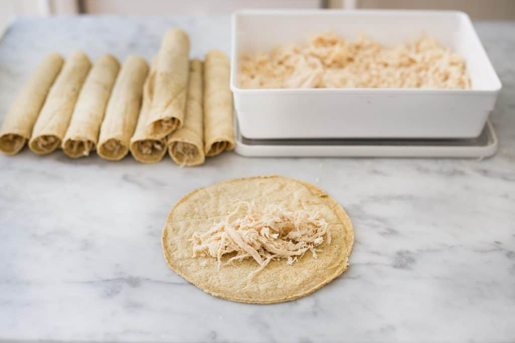 A tortilla flat on a surface with some shredded chicken in the middle.