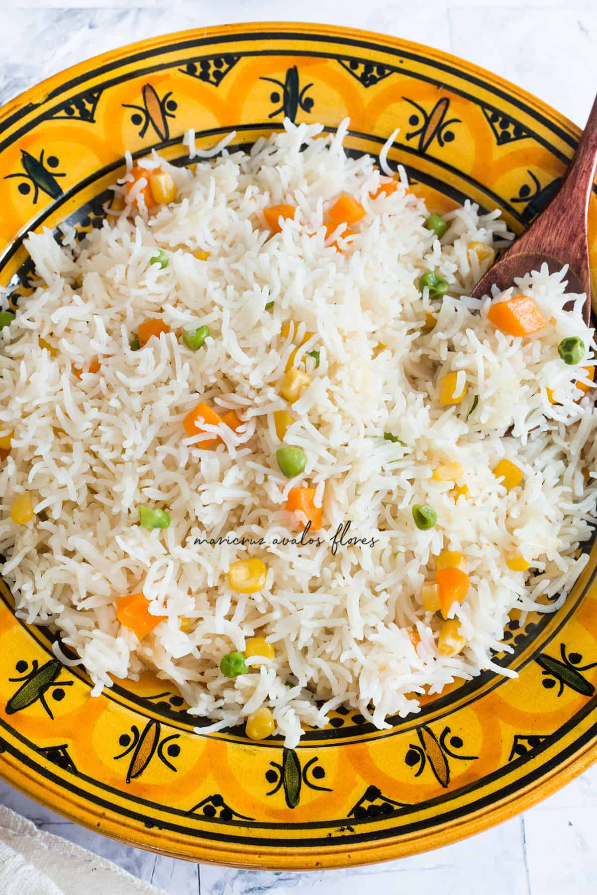 A yellow plate containing white rice with vegetables. Seen from above.