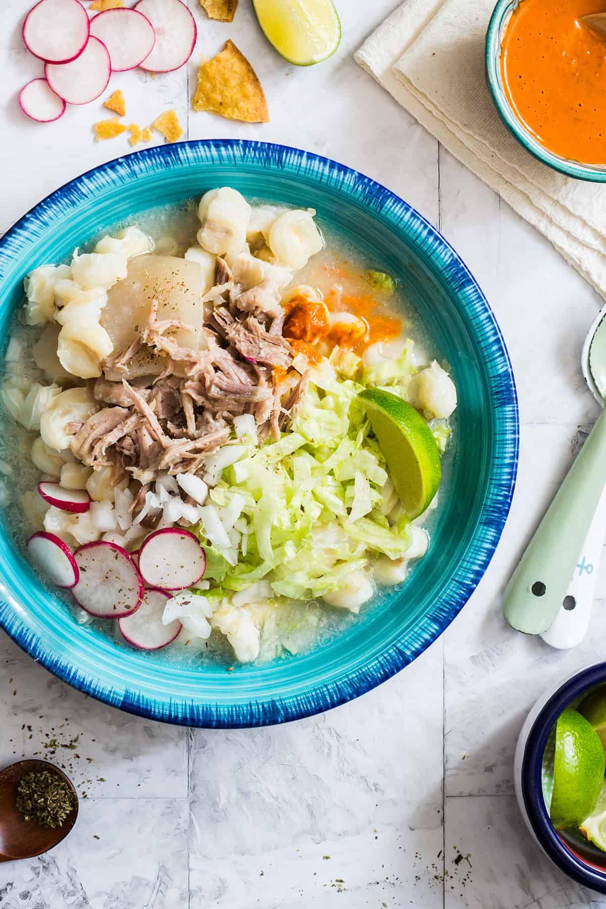 Pozole bianco servito in un piatto turchese