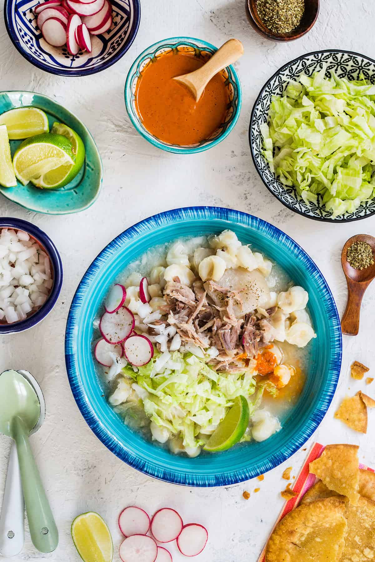 White pozole served with various toppings.