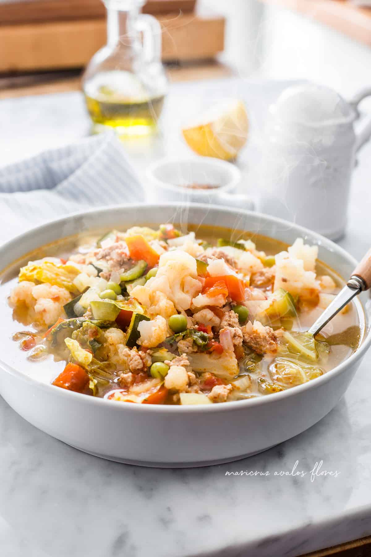 Minestrone soup with sausage served on a deep plate.