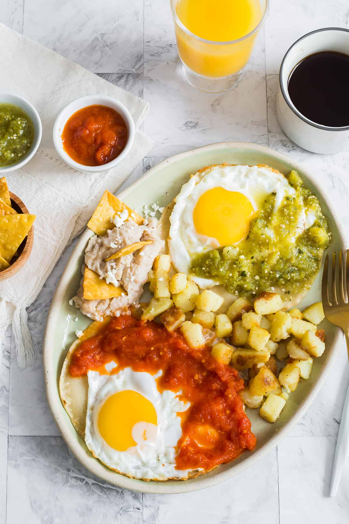 Huevos divorciados served on an oval plate and accompanied with refried beans and potatoes.