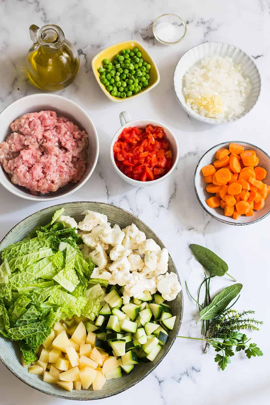Ingredients for minestrone soup with sausage displayed on a marble countertop.