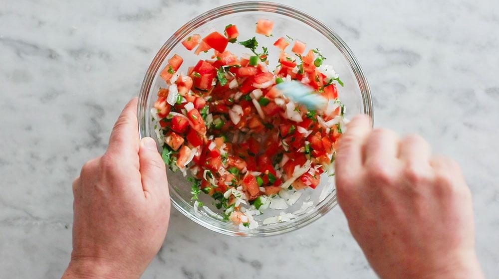 Preparing pico de gallo on a bowl.