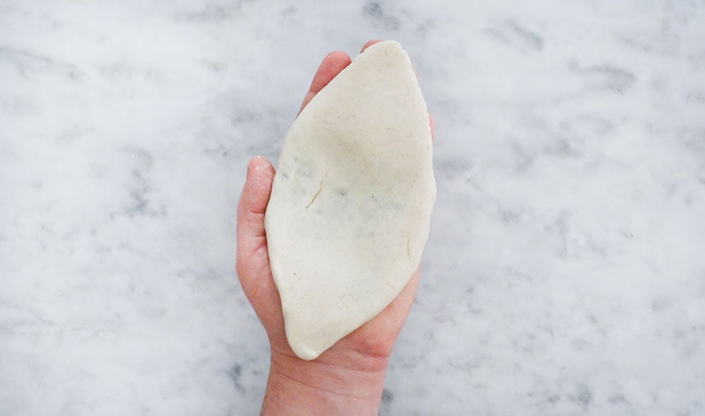A hand holding a shaped tlacoyo.