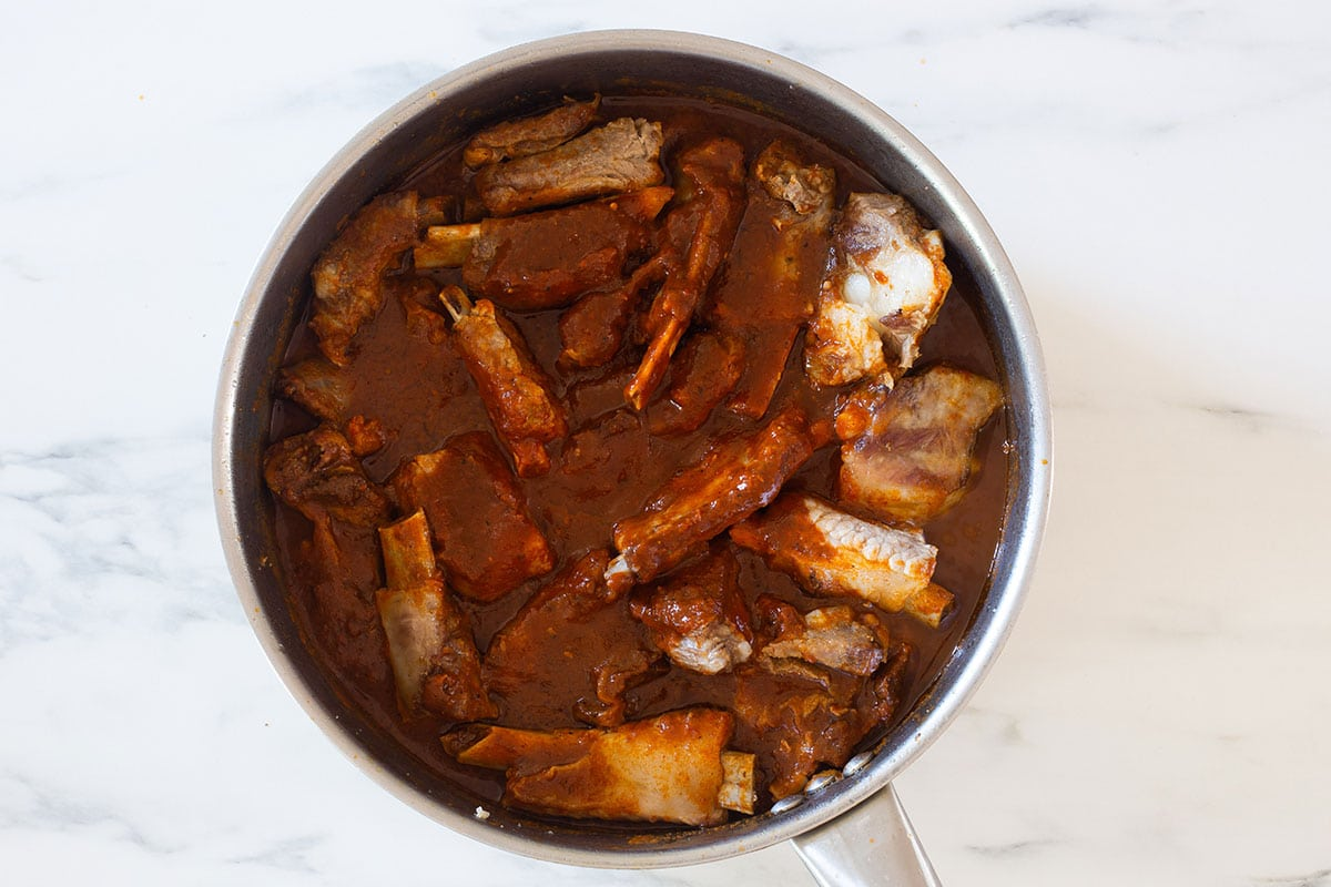 Adobo sauce added to the pan with ribs.