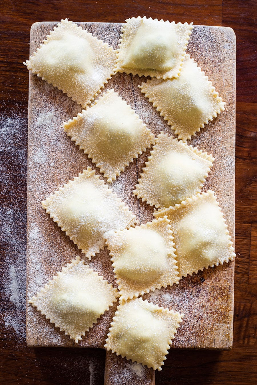 Uncooked ravioli on a cutting board.