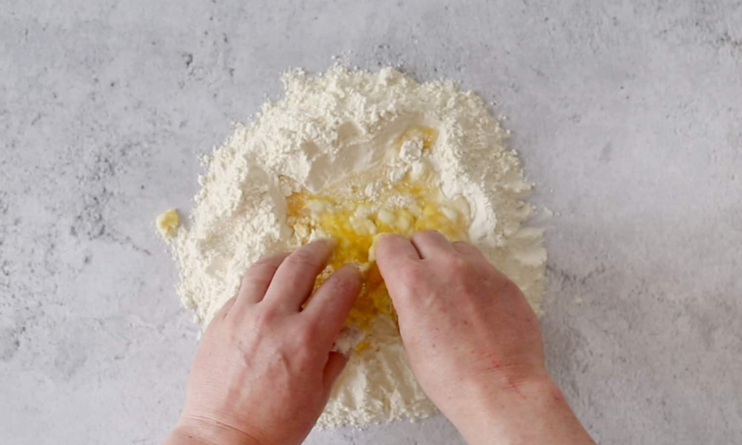 Mixing the flour with eggs.