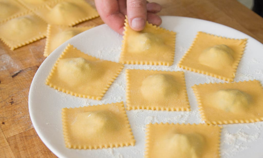 Placing the spinach and ricotta ravioli on a floured plate.