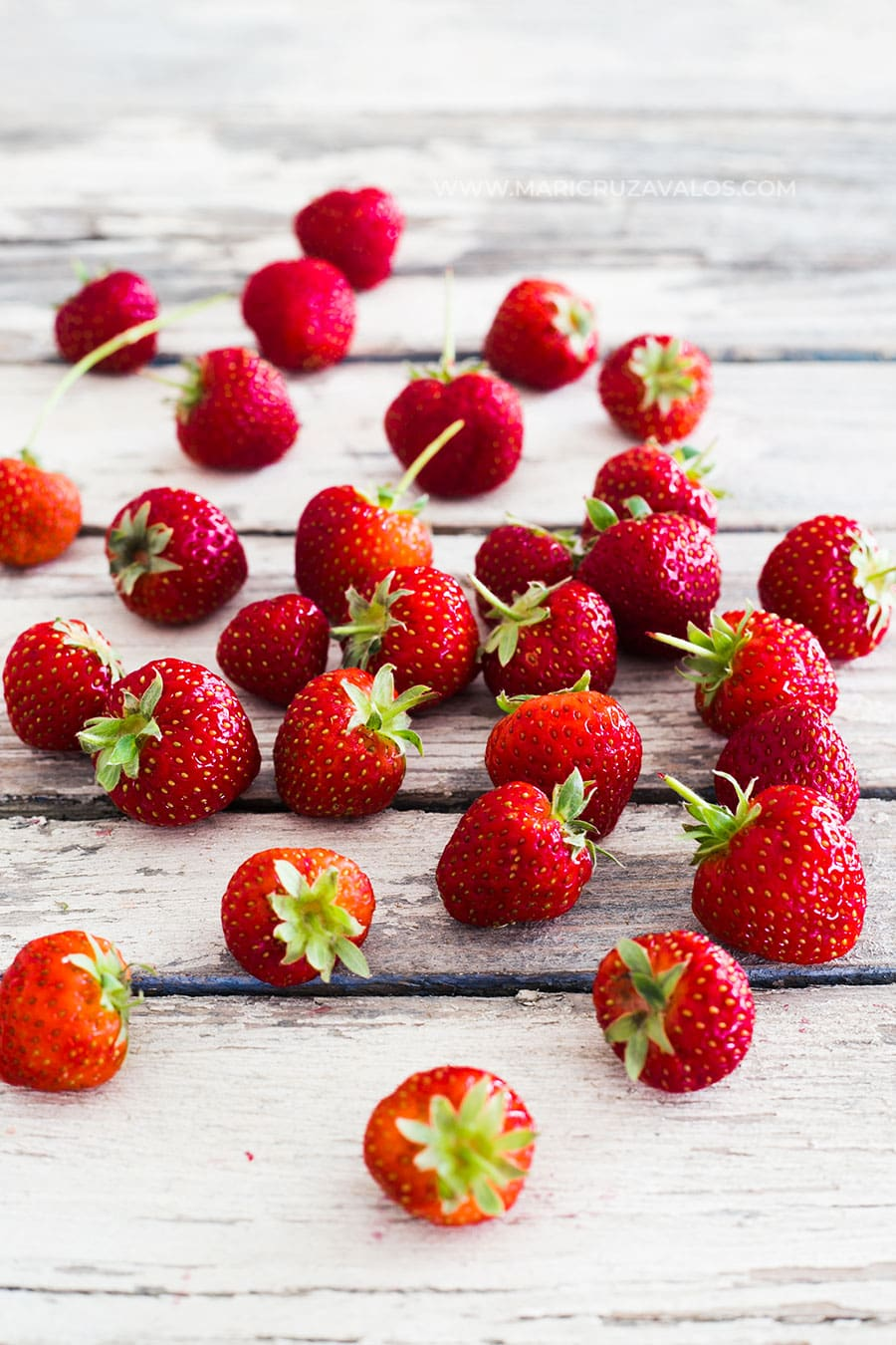Fresh strawberries on a white wooden table.