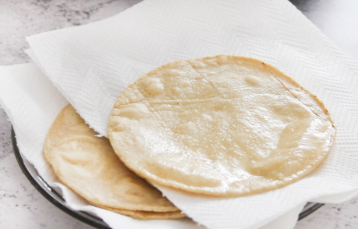 Some fried tortillas placed between paper kitchen towels.