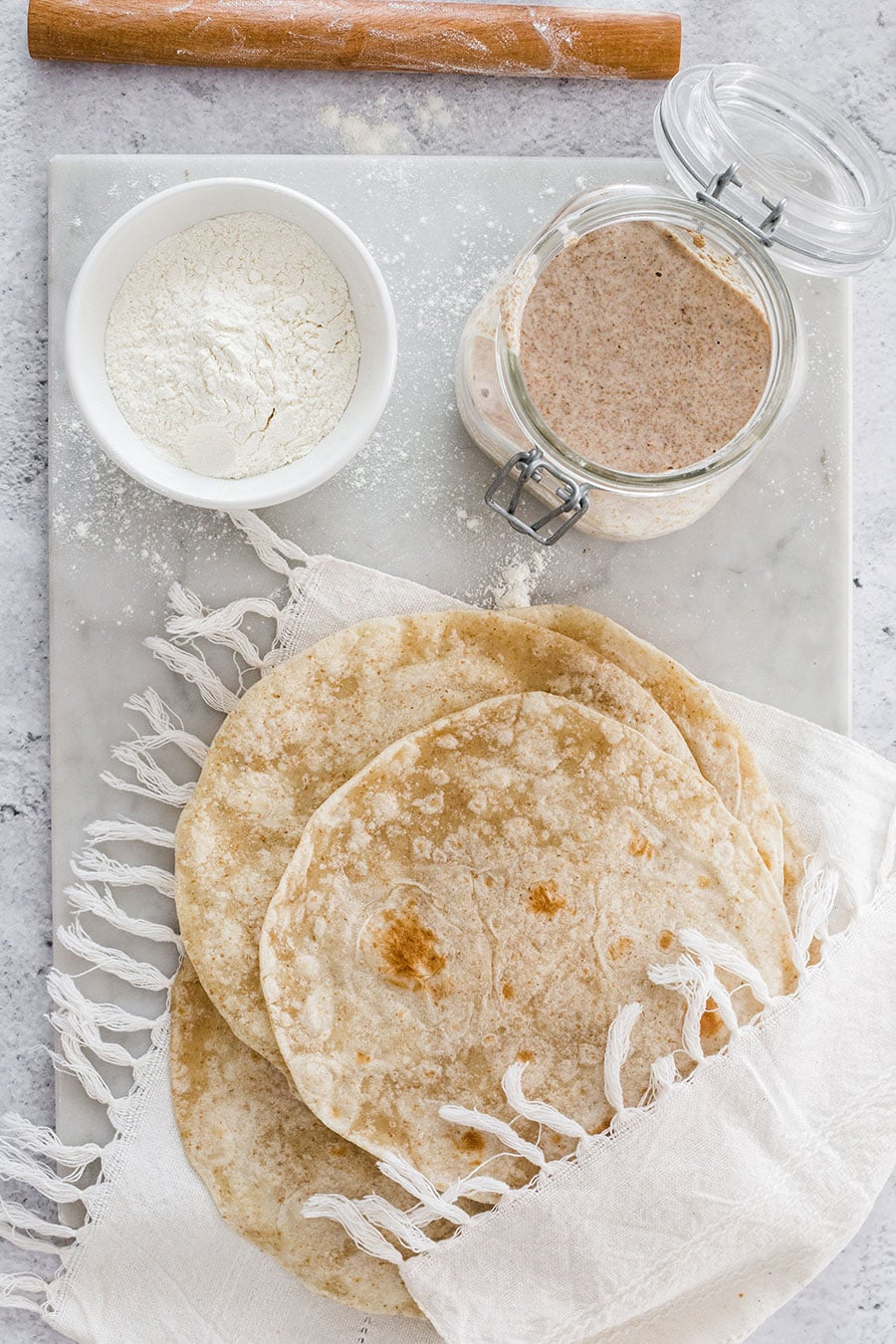 Flour tortillas from above and a sourdough jar near by.