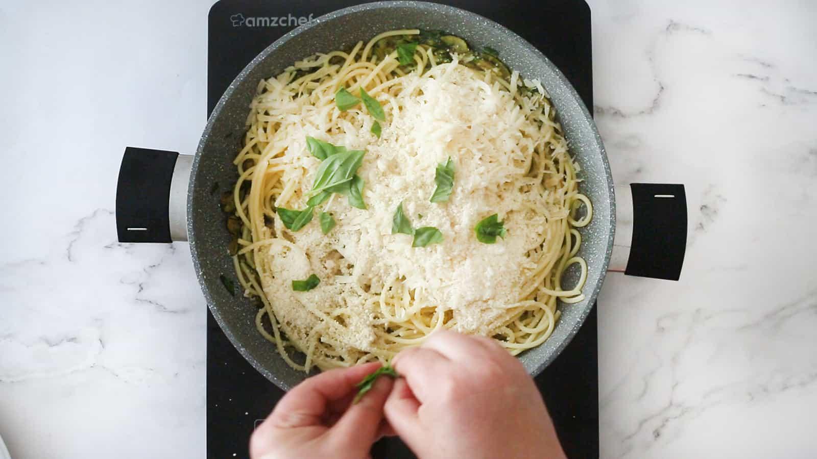 Adding hand-torn basil to the pan.