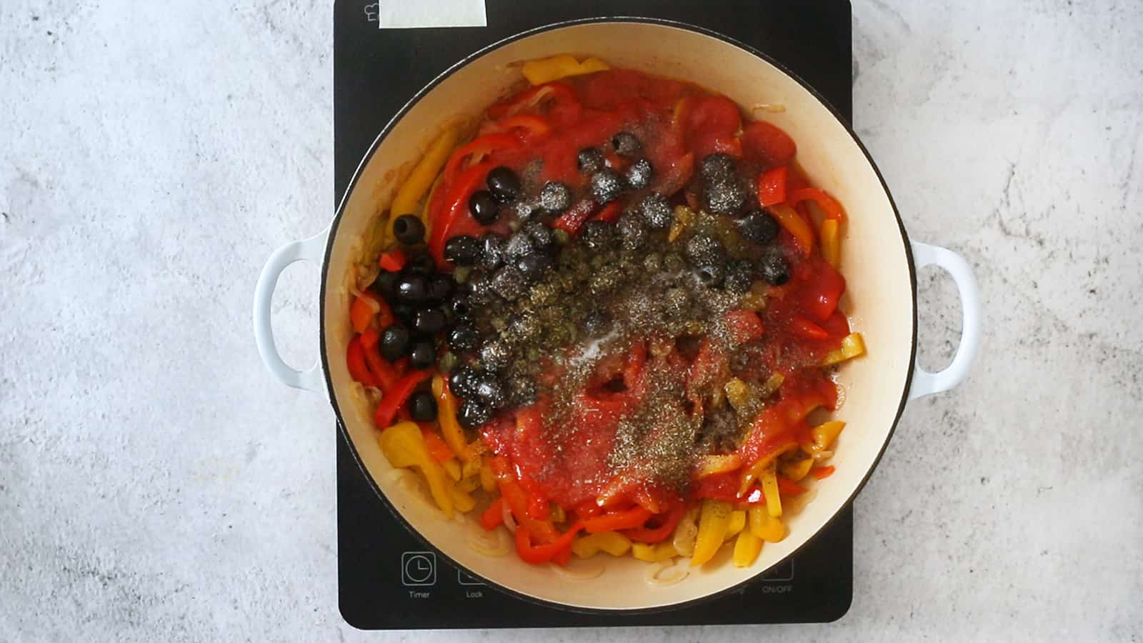 Olives, capers and oregano added to the pan.