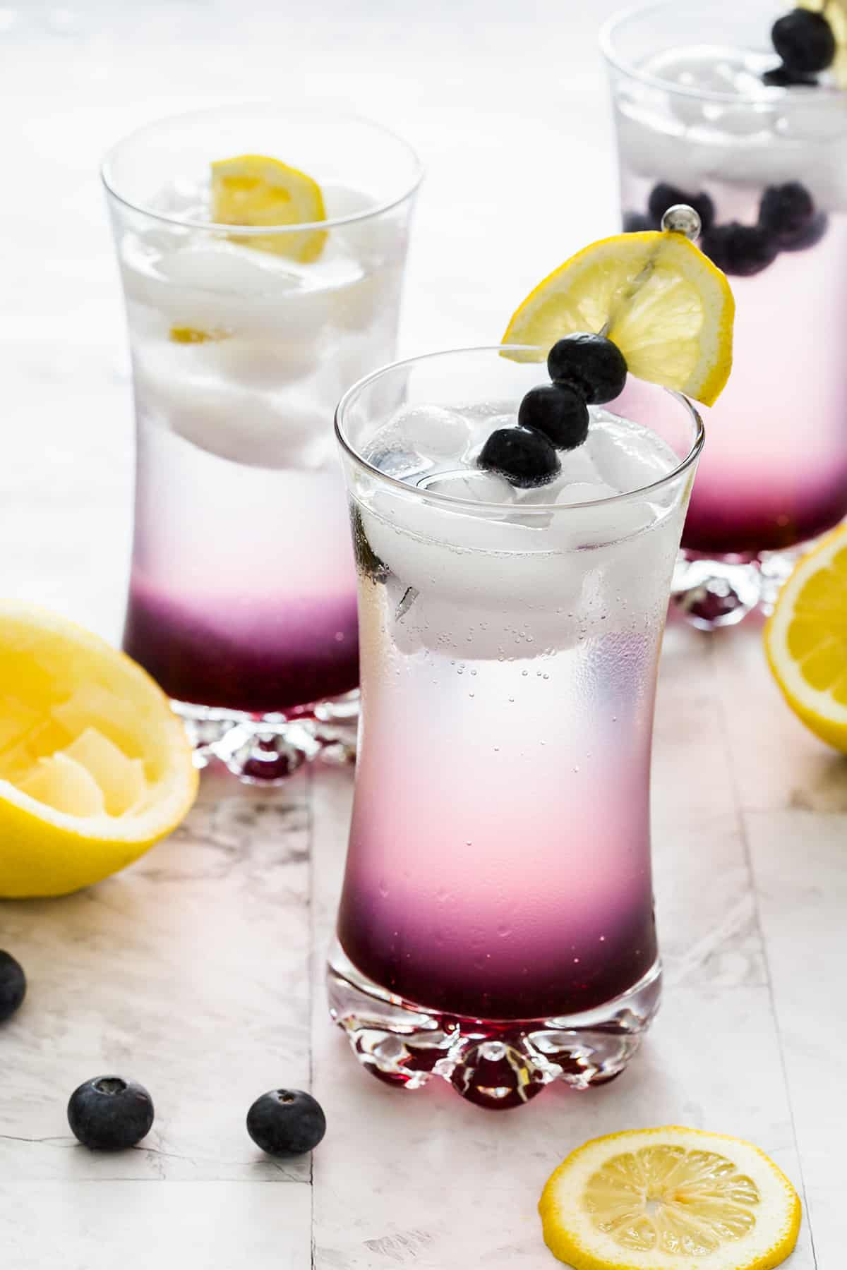 Three glasses with blueberry and lemonade cocktail.