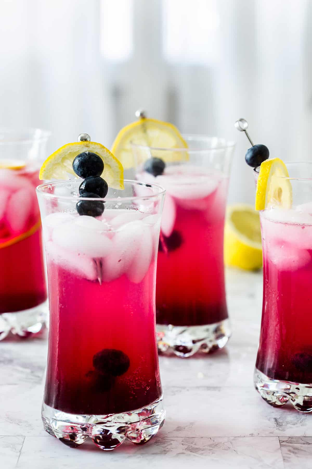 The blueberry vodka lemonade cocktail after mixed, showing a bright red-ish hue.