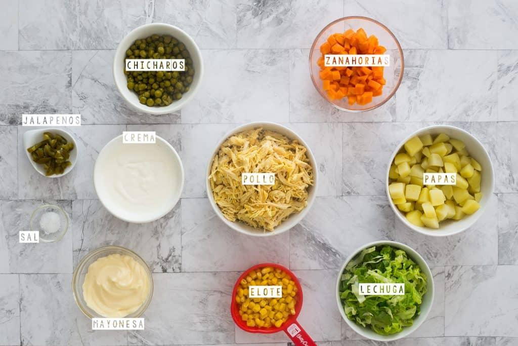 Ingredientes para la ensalada de papas y pollo puestos en cuencos sobre una mesa de mármol.