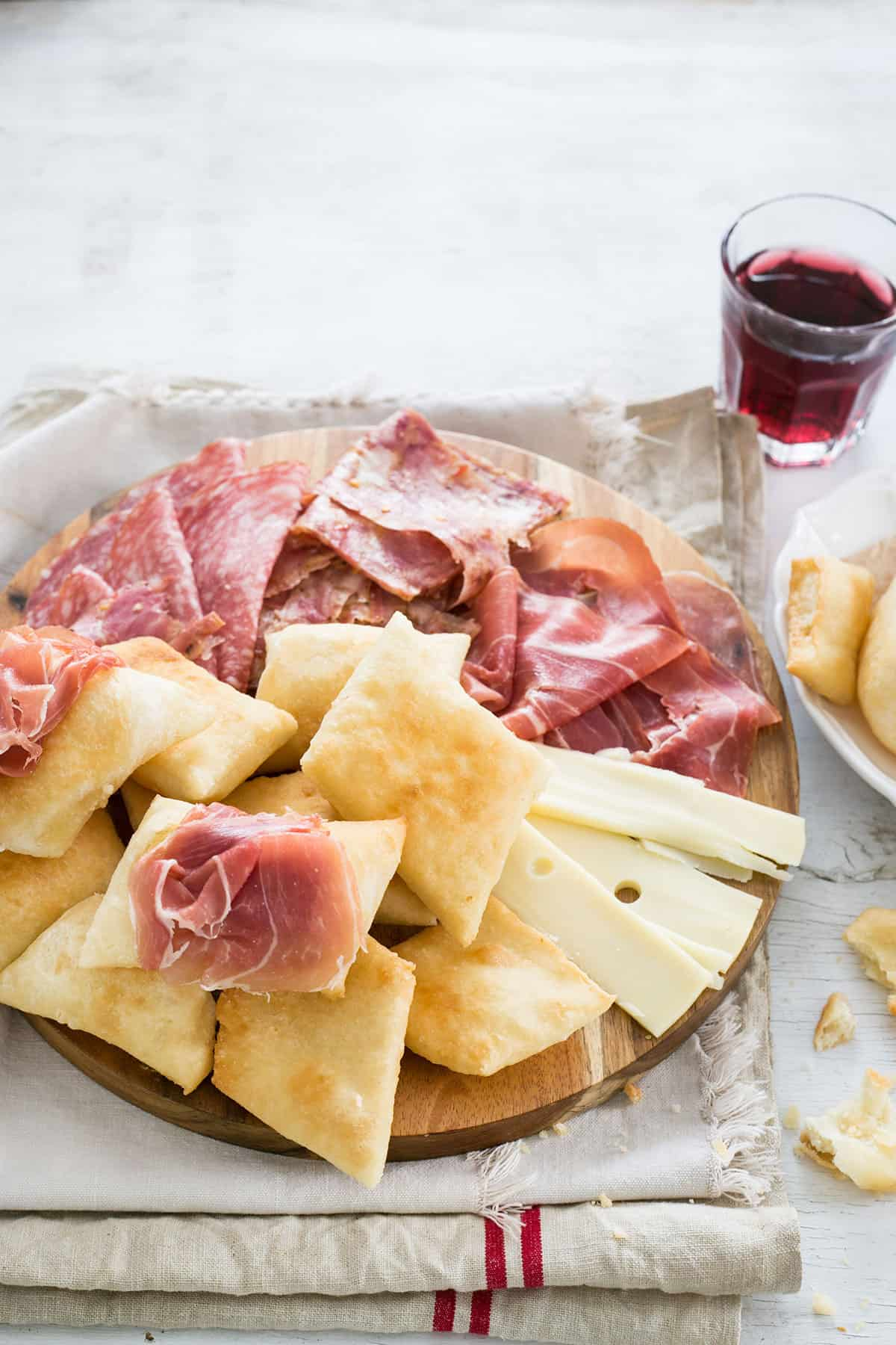 Gnocco fritto served with various cold cuts and cheese on a cutting board.
