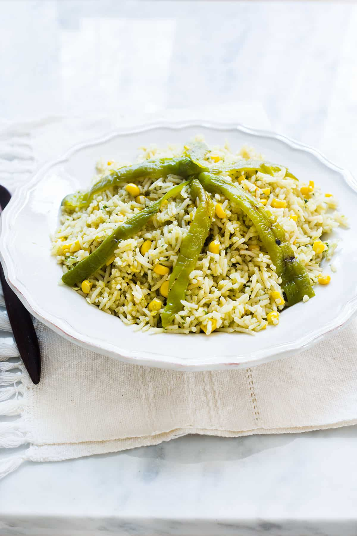 Mexican green rice (arroz verde) topped with poblano peppers strips.