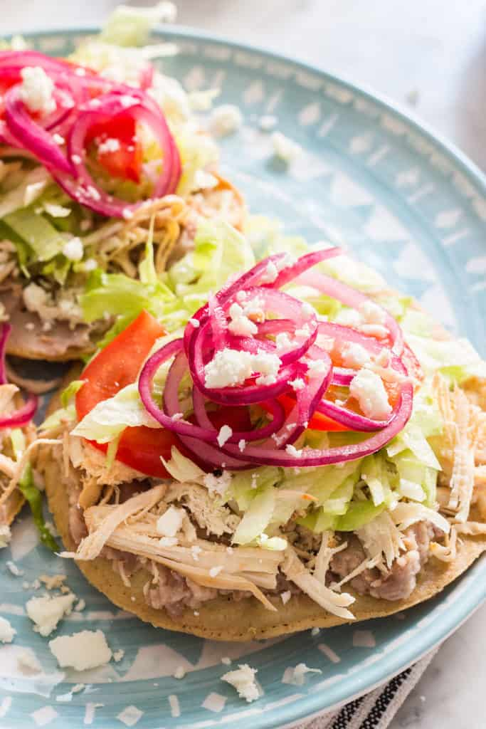 Chicken tostadas served with refried beans, lettuce, fresh tomatoes and pickled onions. Yummy!