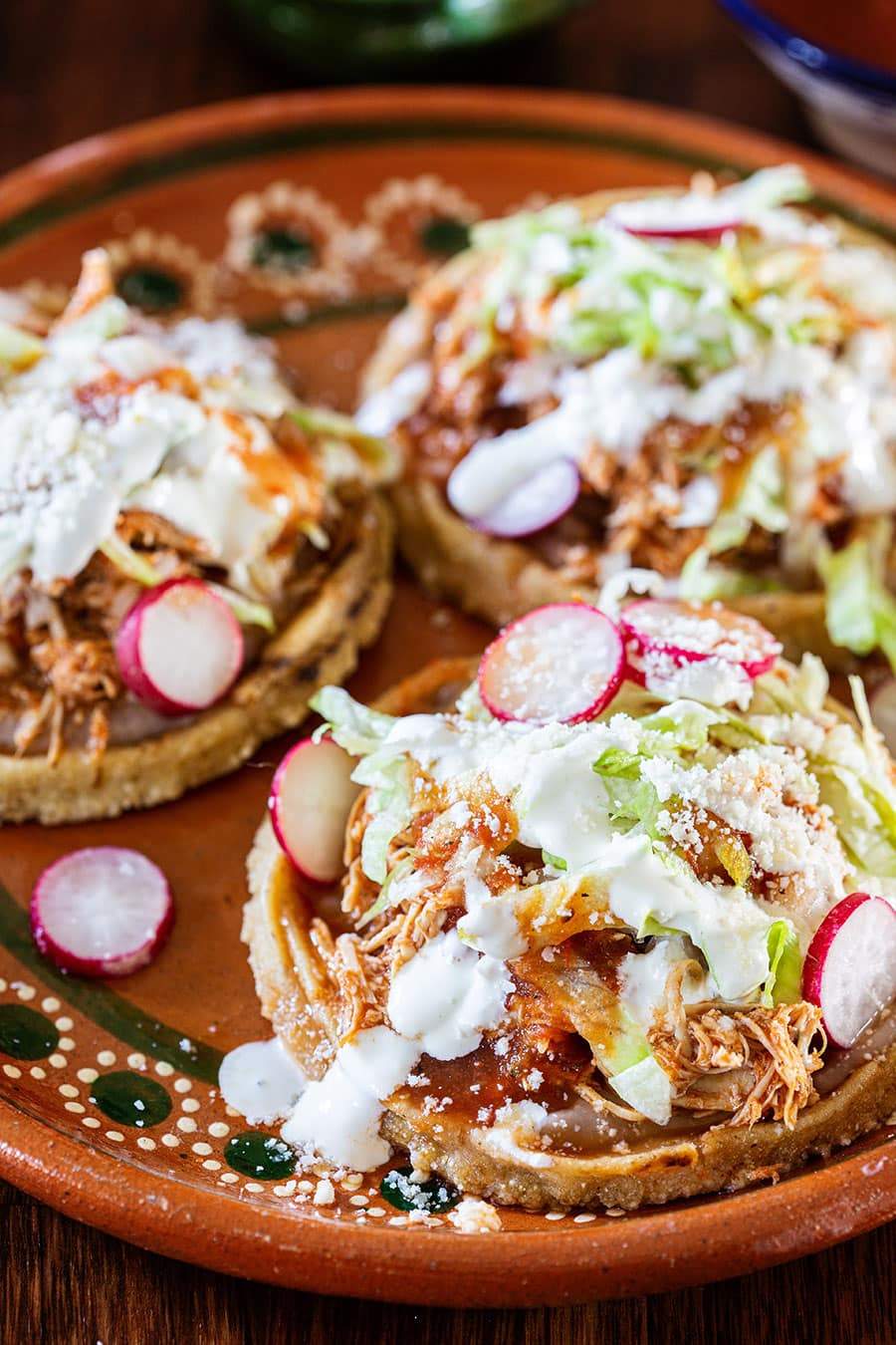 Mexican sopes de pollo served with various toppings.