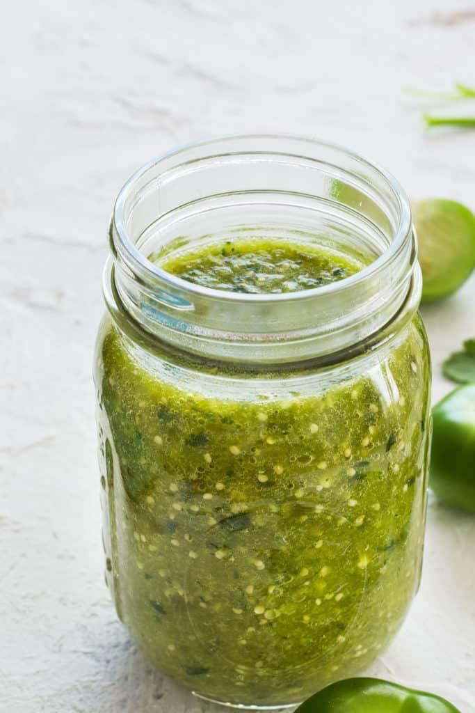 Salsa verde receta mexicana. Frasco con salsa verde de tomatillo.