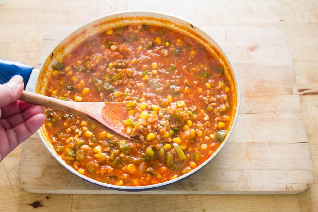 Una cuchara mostrando un poco de la carne preparada con salsa y verduras ya lista para preparar los tacos tex mex.