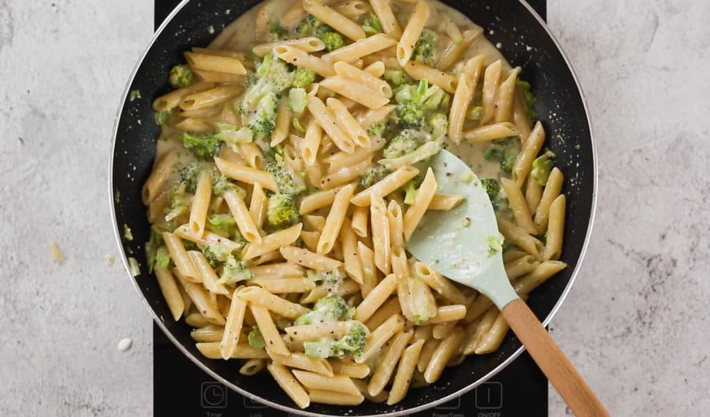 Penne rigate being tossed with broccoli creamy sauce on a pan.