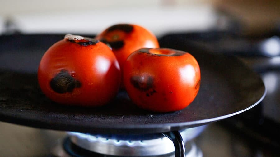 Roasting tomatoes on a comal.