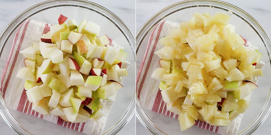 The apples and pineapple on a large bowl.