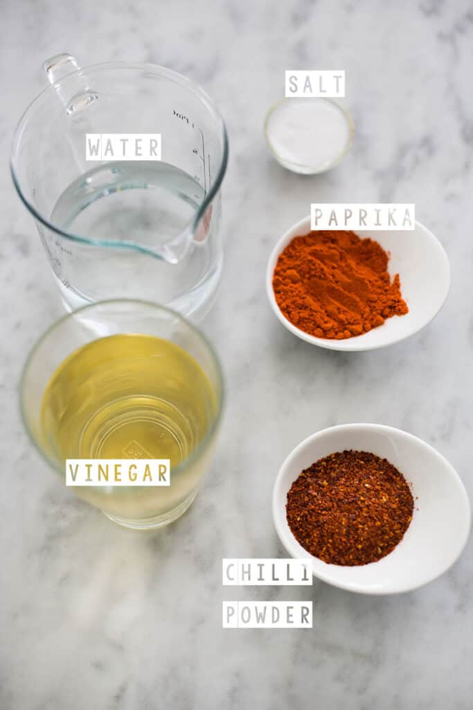 Homemade Valentina sauce (copycat) ingredients displayed on a marble surface.