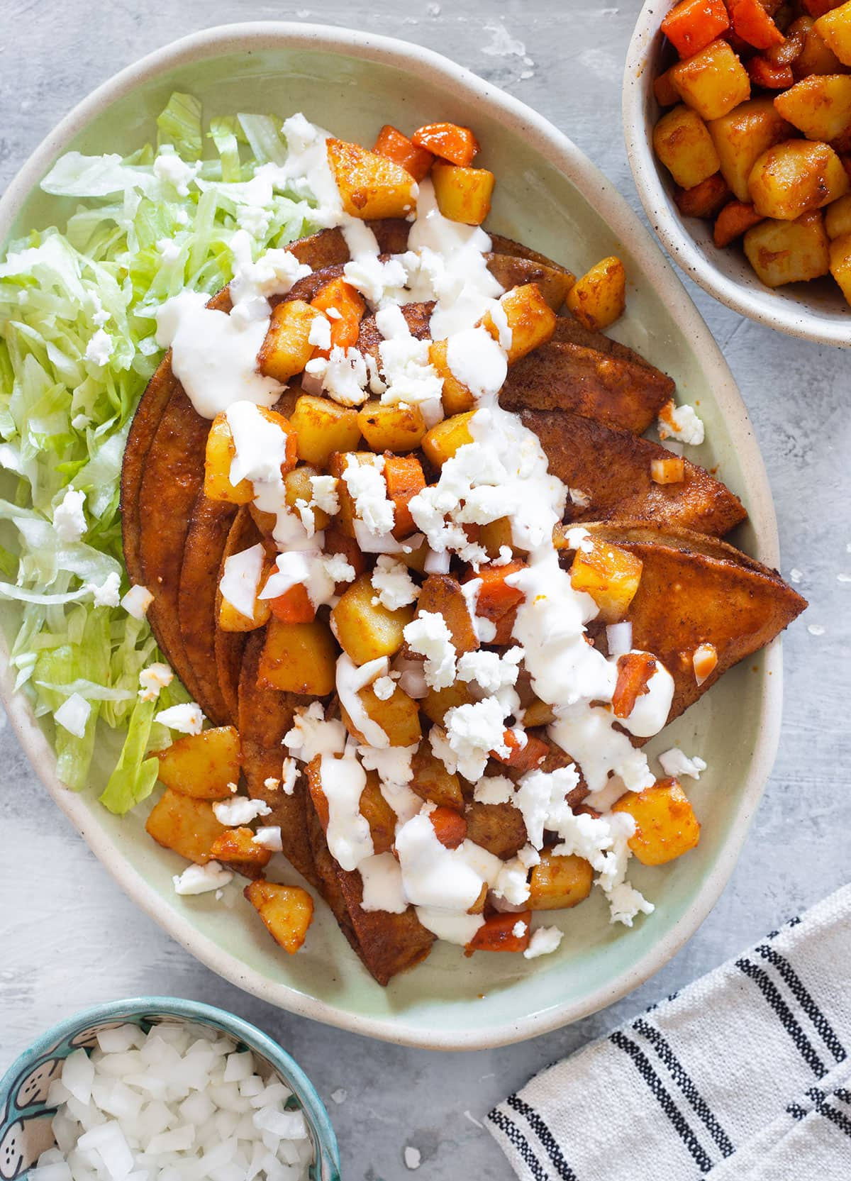A plate with chicken enchiladas topped with sautéed potatoes and carrots, queso fresco, and cream.